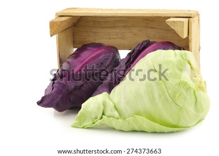 red and green pointed cabbage in a wooden crate on a white background - stock photo