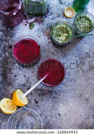 Red and green smoothies and lemon over an dark metal background. Beetroot and vegetables smoothies. Rustic style. Healthy and summer food concept. Top view.  - stock photo