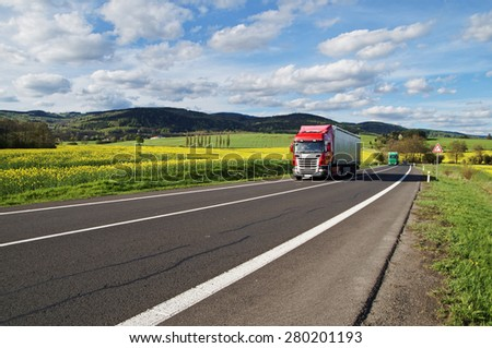 Red and green trucks arrives on an asphalt road between the yellow flowering rapeseed field in the rural landscape. Wooded mountains in the background. Blue sky with white clouds. - stock photo