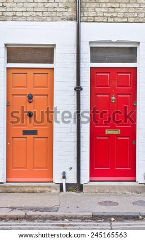 Red and orange front doors on adjoining terraced homes in the UK - stock photo