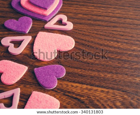 red and pink hearts on a wooden background, place for text Love background - stock photo