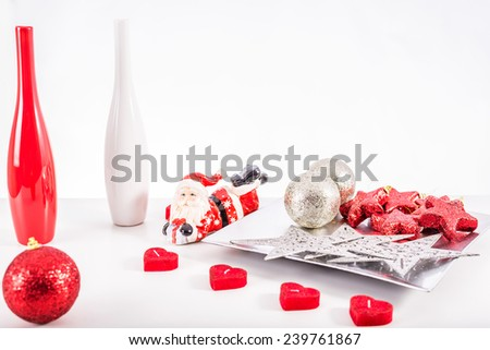 Red and silver christmas balls and stars on a silver decoration tray with a red and white decoration vases on a white background - stock photo