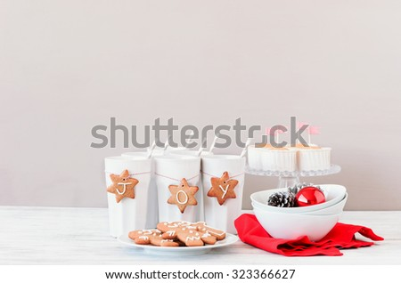 Red and white christmas table decoration setting with gingerbread stars tied with bakers twine to cups as ornaments - stock photo