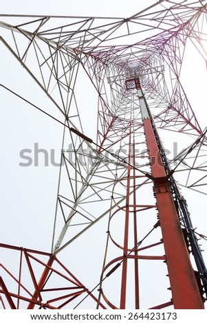 red and white color antenna repeater tower from bottom view on white sky - stock photo