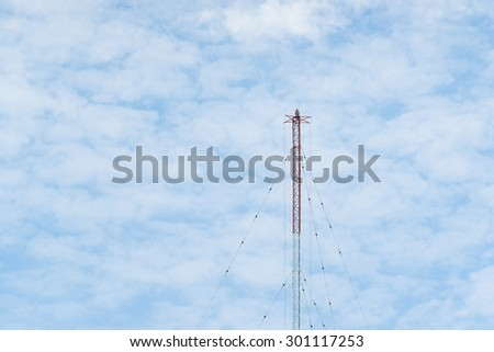 Red and white communication tower with GSM antenna transmitters. - stock photo