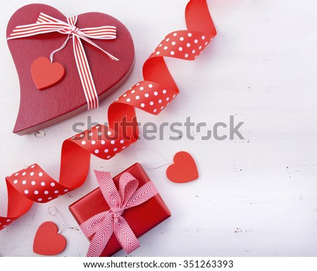 Red and white, festive holiday background with gifts, ribbons, hearts on a white wood table with copy space for your text here.  - stock photo