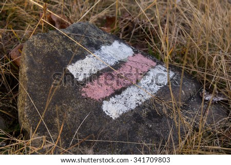 red and white hike path symbol in the mountains - stock photo