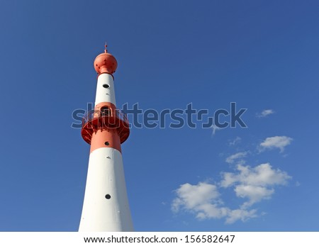 Red and white lighthouse against blue sky - stock photo