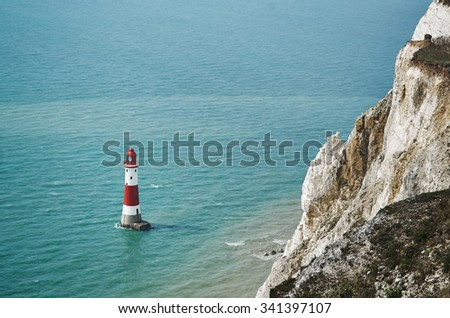 Red and white lighthouse in the sea with rock - stock photo