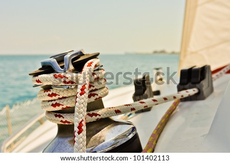 Red and white line wrapped around winch of sailboat - stock photo