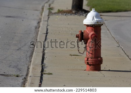 Red and white painted fire hydrant standing watch on a city street. - stock photo
