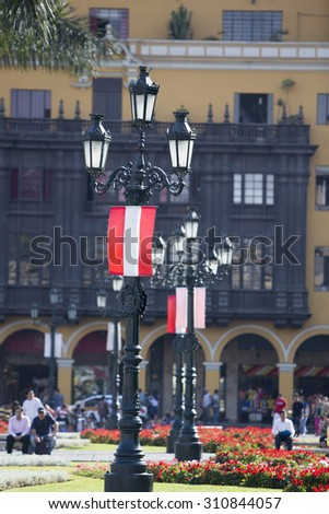 Red and white Peruvian flag hanging to an antique belvedere on Plaza de Armas (Weapons Square), blue sky and old colonial architecture in the background, Peru - stock photo