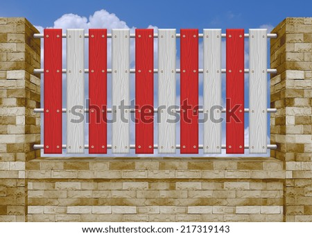 Red and white  picket fence, brick wall. - stock photo