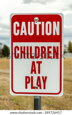 Red and white sign to warn motorists to slow down because there might be children playing near the road - stock photo