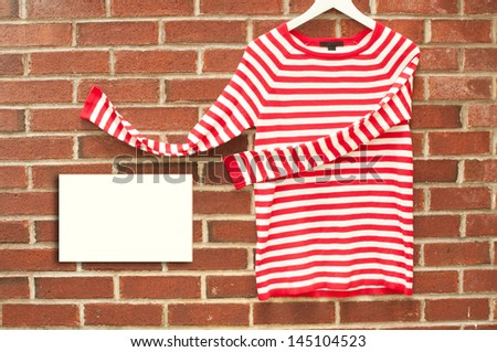 Red and white striped shirt inviting with sign copyspace  - stock photo
