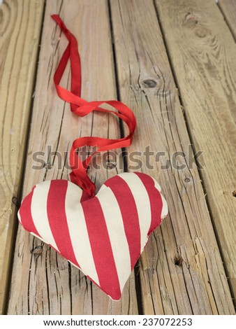 red and white striped textile heart with red ribbon against an aged knotted cracked  wooden background - stock photo