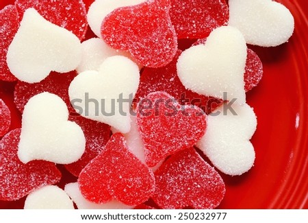 Red and White sugared candy hearts on a red plate for Valentine's Day - stock photo