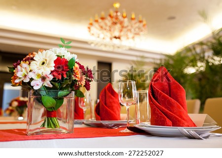 Red and white table of food and glasses - stock photo