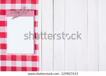 Red and white tablecloth, recipe book on wooden background - stock photo