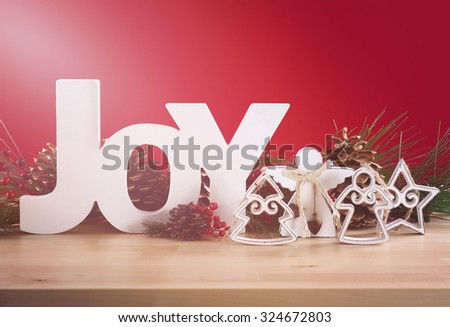 Red and white theme Christmas table decorations and wood Joy letters and added vintage style filters and lens flare light stream.  - stock photo