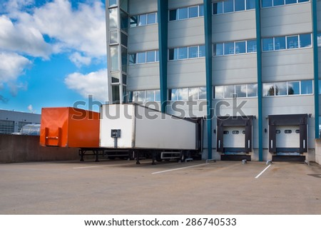 Red and White Trailer at a Docking Bay of a distribution centre, ready for Transport - stock photo
