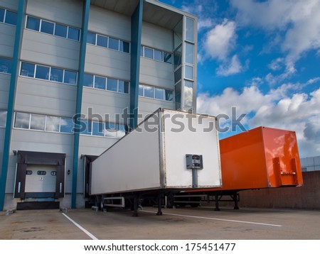 Red and White Trailer in Front of Docking Bay ready for Transport - stock photo