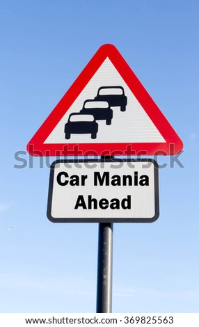 Red and white triangular road sign with a Car Mania Ahead concept against a partly cloudy sky background - stock photo