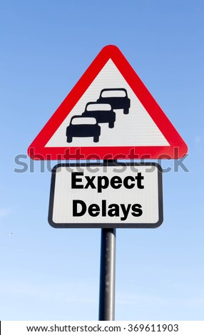 Red and white triangular road sign with an Expect Delays Ahead concept against a partly cloudy sky background - stock photo