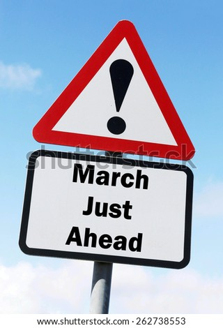 Red and white triangular warning road sign informing that March is Just Ahead concept against a partly cloudy sky background - stock photo