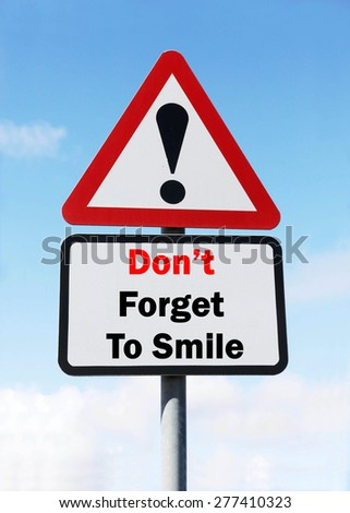 Red and White triangular warning road sign with a Don't Forget to Smile concept against a partly cloudy sky background. - stock photo