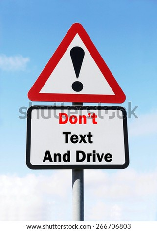 Red and White triangular warning road sign with a Don't Text And Drive concept against a partly cloudy sky background. - stock photo