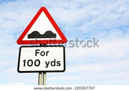 Red and white triangular warning road sign with a warning of a bumpy road ahead concept against a partly cloudy sky background - stock photo