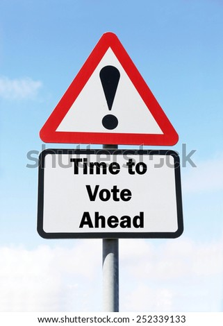Red and white triangular warning road sign with a warning of the Time to Vote Ahead during an election campaign concept against a partly cloudy sky background - stock photo