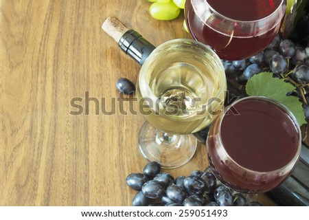 Red and white wine and grapes with fresh leaves on wooden background  - stock photo