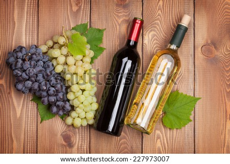 Red and white wine bottles and bunch of grapes on wooden table - stock photo