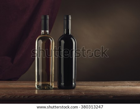 Red and white wine bottles on a rustic wooden table, drape on background, wine tasting still life - stock photo
