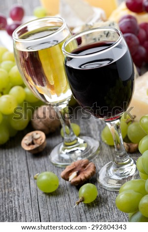 red and white wine, grapes, nuts and cheeses, close-up - stock photo
