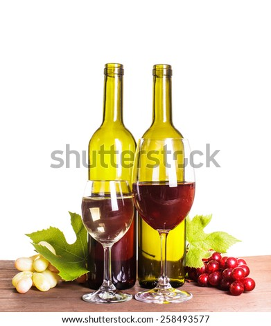 Red and white wine in bottles and glass on the wooden table - stock photo