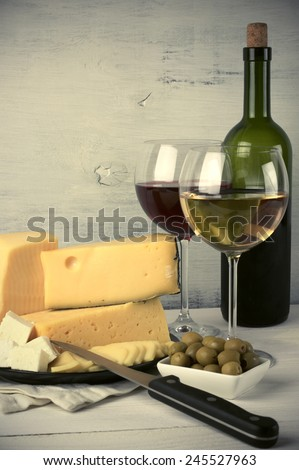 Red and white wine in glasses and bottle and assorted cheese with olives on rustic wooden background. Toned image. - stock photo