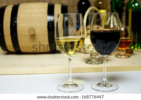 Red and white wine in glasses, brandy. On the background of a barrel and wine corks basket, bowl with cheese and a bottle of wine, a corkscrew. - stock photo