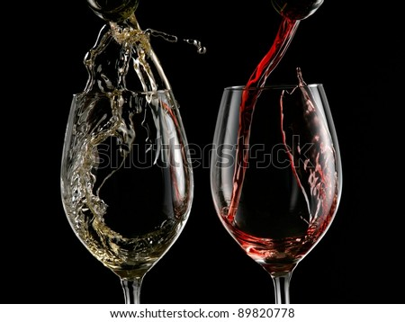 Red and white wine start pouring into two wineglasses on black background - stock photo