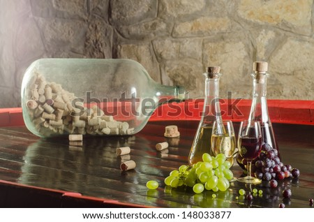 Red and white wine with glasses and bunches of grapes - stock photo