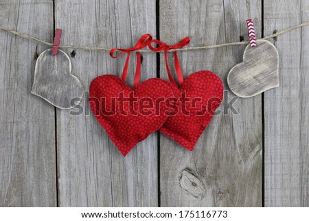 Red and wood hearts hanging on clothesline with wood background - stock photo