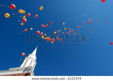 red and yellow balloons floating skyward after a wedding - stock photo