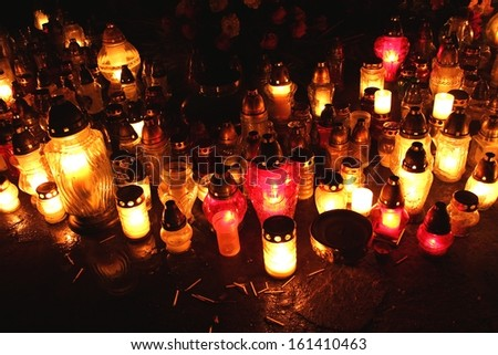 Red and yellow candles flames on grave during All Saint's Day, Poland  - stock photo
