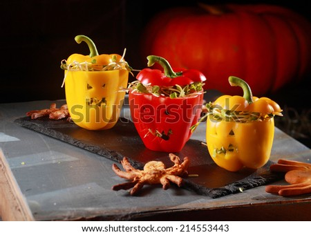 Red and Yellow Peppers with Scary Faces Stuffed with Sprouts with Edible Octopus - stock photo