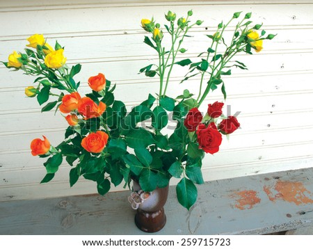 Red and yellow roses in the vase on wooden bench - stock photo