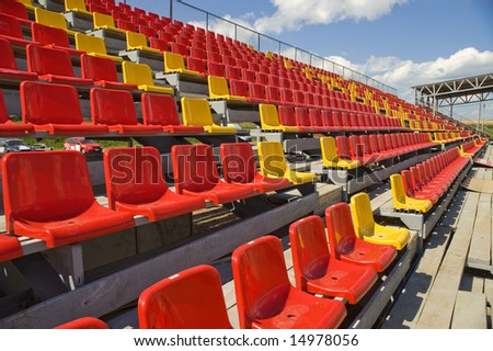 Red and yellow seats on a background of the sky with clouds. - stock photo