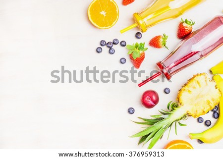 Red and yellow smoothies in bottles with fruits ingredients  on white wooden background, top view, place for text.  Superfoods and healthy lifestyle or detox  diet food concept. - stock photo
