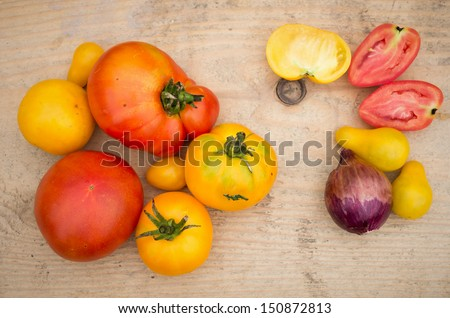 red and yellow tomatoes on wooden board - stock photo